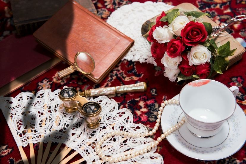 Various clues to a crime laid out on a table, a teacup with a lipstick mark, roses, a journal, a mag